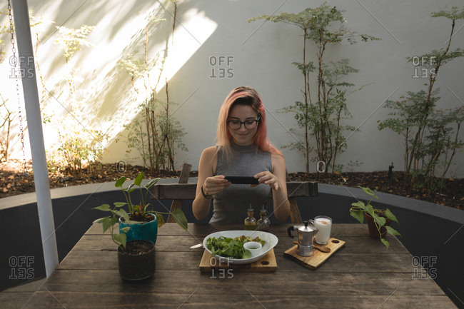 Young woman photographing food served on table in a coffee shop
