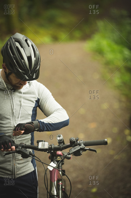 Cyclist checking time on smartwatch in forest