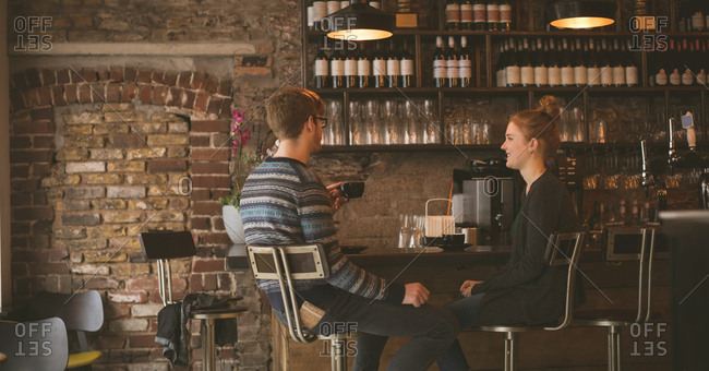 Young couple having coffee while sitting at the bar counter