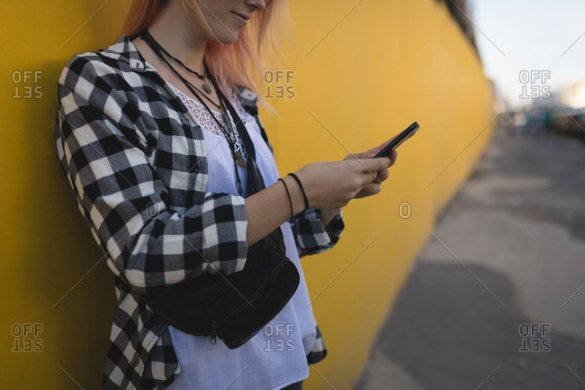 Young woman using a mobile phone at pavement