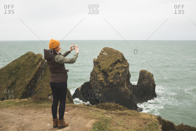 Young female hiker photographing the sea