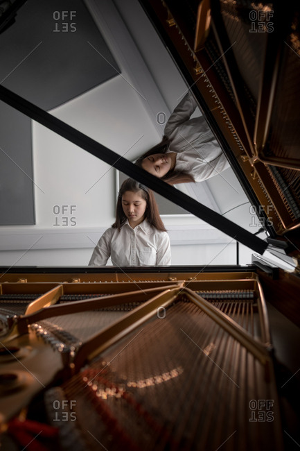 Adorable schoolgirl playing piano in music school