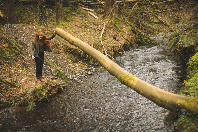 Beautiful female hiker looking at the shallow river in the forest