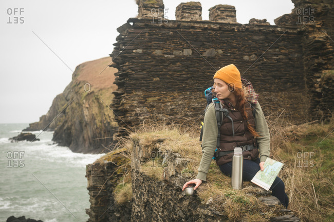 Beautiful female hiker with map looking at sea