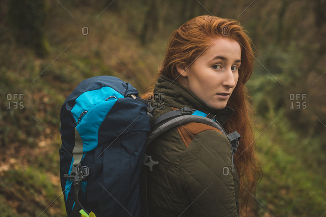 Portrait of beautiful female hiker with backpack looking into camera