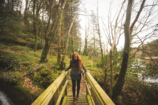 Red hair female hiker walking on bridge in the forest