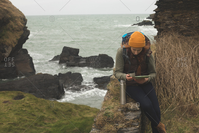 Concentrated female hiker reading a map and having a drink