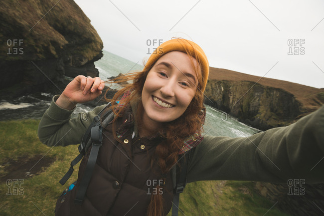 Portrait of smiling female hiker having fun near the sea