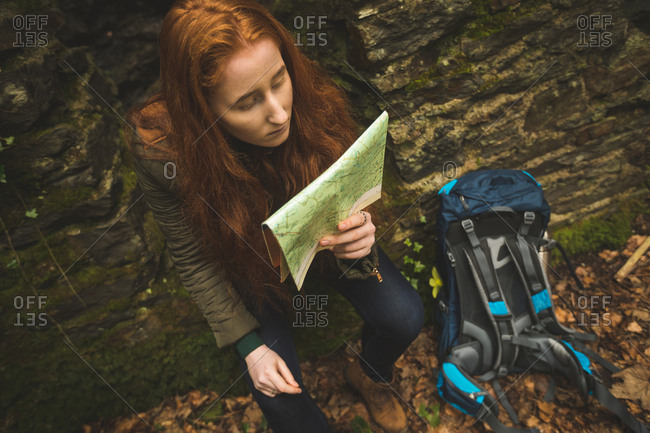 Red hair female hiker with backpack reading a map in the forest