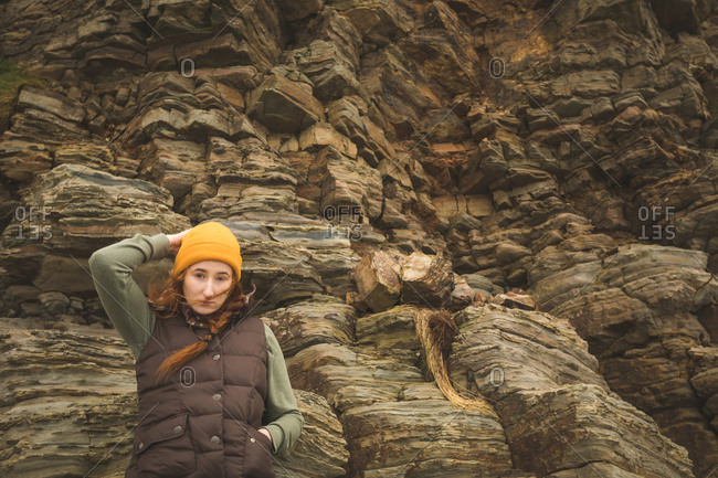 Beautiful female hiker leaning against the rock