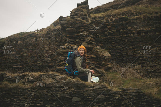 Side view of female hiker sitting on the abandoned stone wall