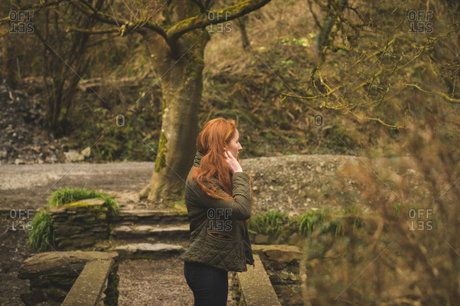 Beautiful red hair female hiker looking around in the forest