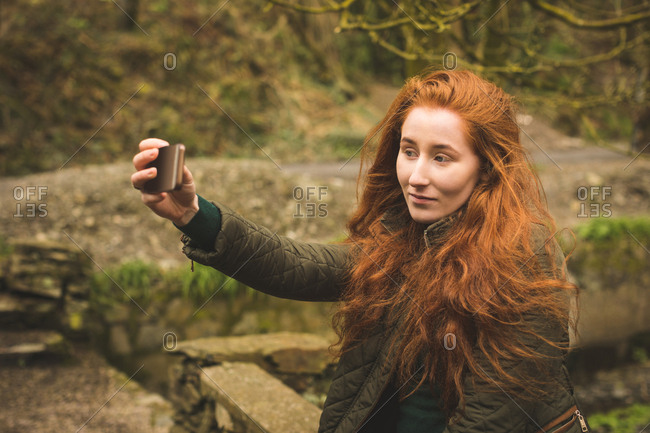 Beautiful female hiker taking selfie with mobile phone in the forest