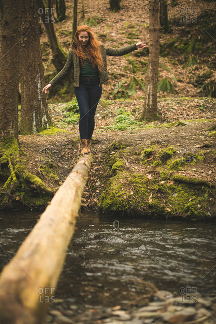 Female hiker walking on the fallen tree trunk across the river in the forest