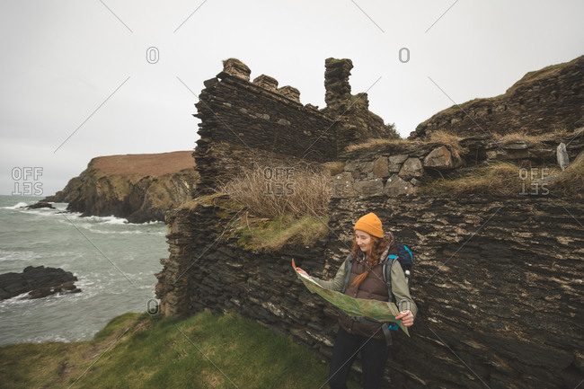 Beautiful female hiker leaning against the rock and reading a map