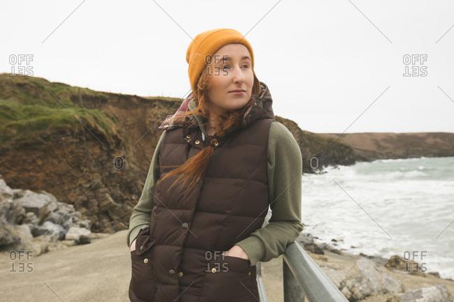 Beautiful female hike leaning against the railing near the sea