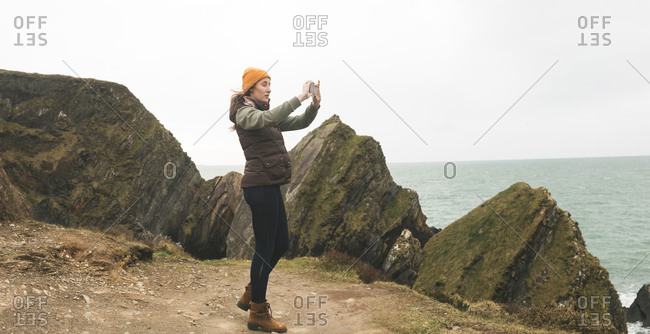 Side view of female hiker photographing the sea