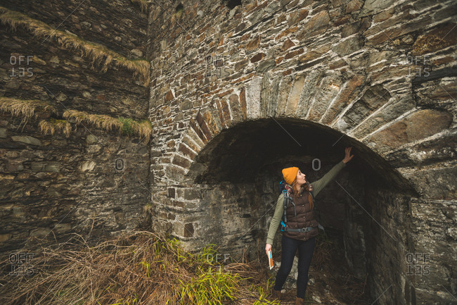 Young female hiker touching the wall