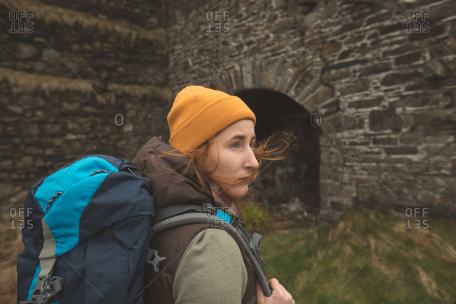 Beautiful female hiker with backpack looking around