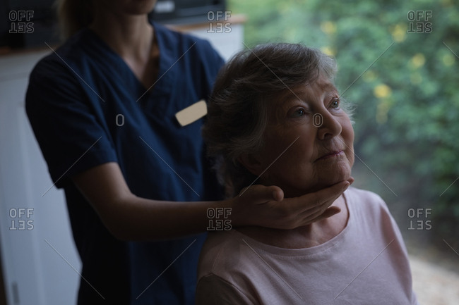 Physiotherapist giving a neck massage to senior woman at home