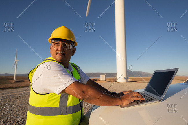 Engineer using a laptop at wind farm