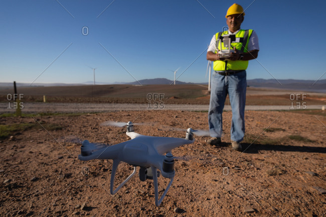 Engineer controlling a drone with a controller at a wind farm