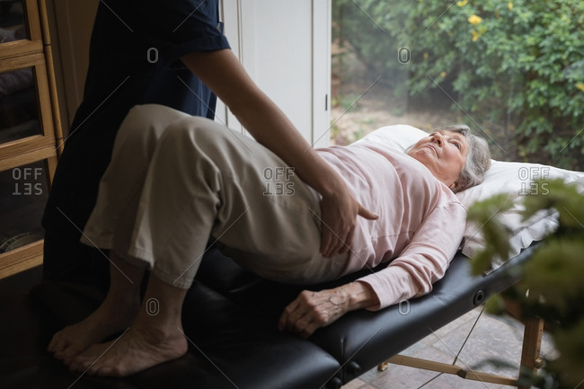 Physiotherapist giving a body massage to senior woman at home