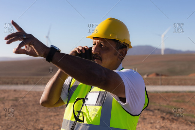 Engineer talking on mobile phone at wind farm