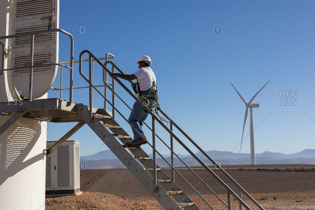 Engineer climbing up the stairs of a wind mill at a wind farm