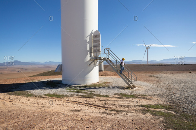 Engineer climbing down the stairs of a wind mill at a wind farm