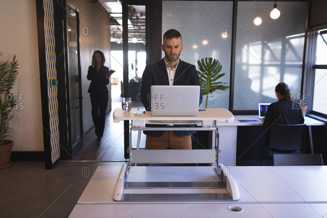 Businessman standing and using laptop at office