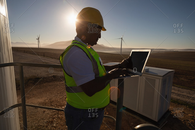 Engineer using a laptop at entrance of a wind mill at a wind farm