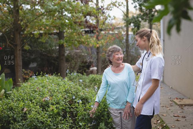 Physiotherapist and senior woman talking at the backyard at home