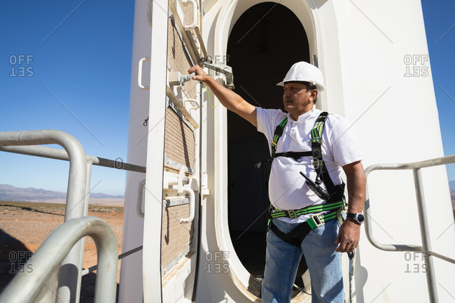 Engineer shutting the door of a wind mill entrance