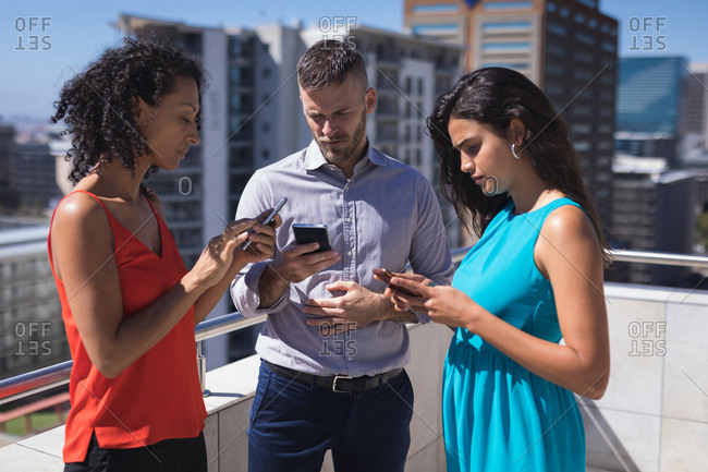Business executives using smartphone at office terrace on a sunny day