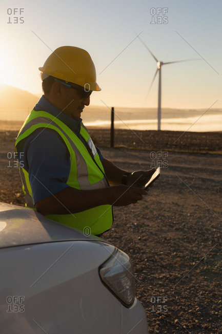 Engineer using a digital tablet at a wind farm