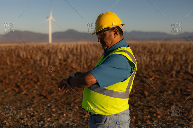 Engineer using a smart watch at a wind farm
