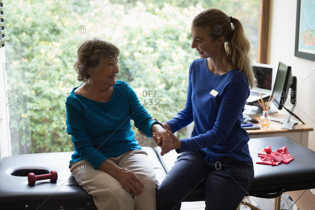Physiotherapist giving a hand massage to a smiling senior woman