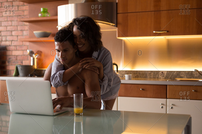 Couple using laptop in kitchen at home