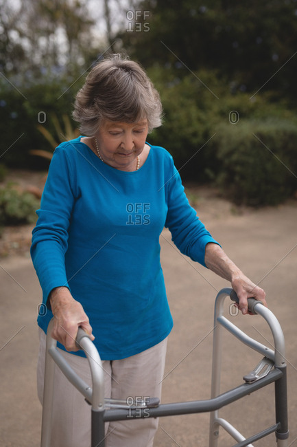 Senior woman walking with the help of walker