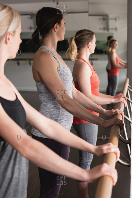 Group of women standing holding the barre at the gym