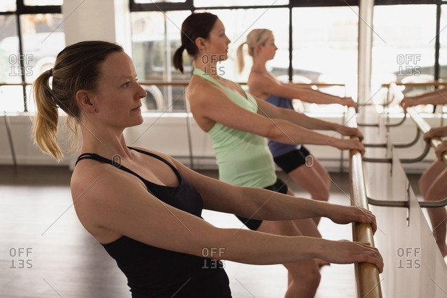 Group of women stretching holding the barre at the gym