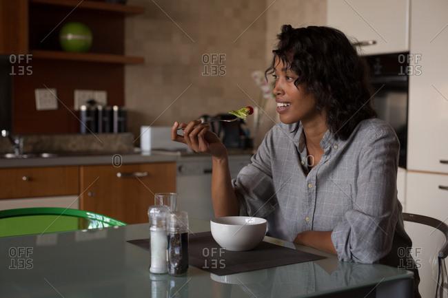 Happy woman having breakfast at home