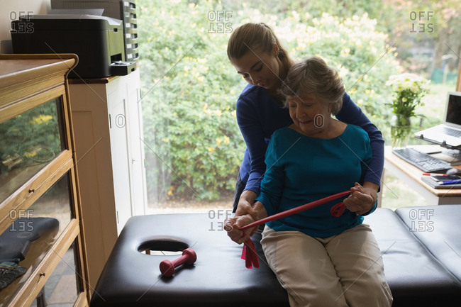 Physiotherapist assisting a senior woman to stretch an elastic band