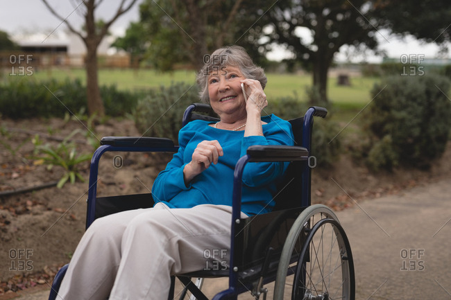 Happy senior woman on wheel chair talking on a mobile phone