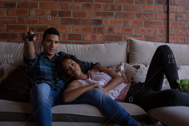 Couple watching television in living room at home