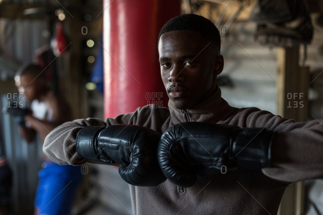 Portrait of male boxer standing with boxing gloves at fitness studio