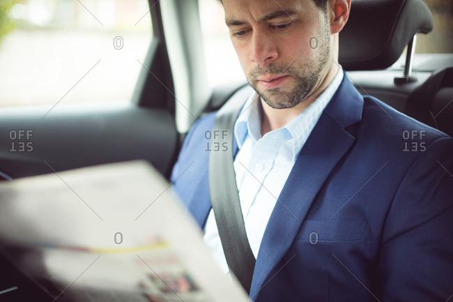 Smart businessman reading newspaper in a car