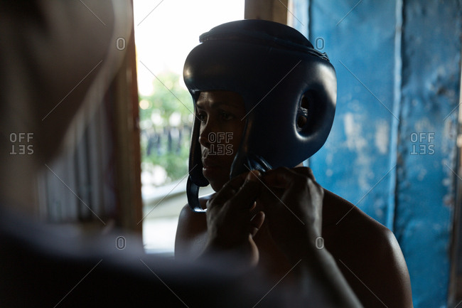 Trainer assisting male boxer to wear headgear in fitness studio