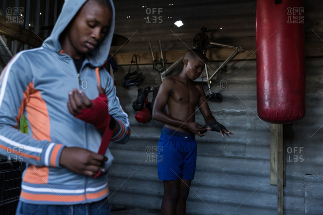 Male boxer tying hand wrap on hand at fitness studio